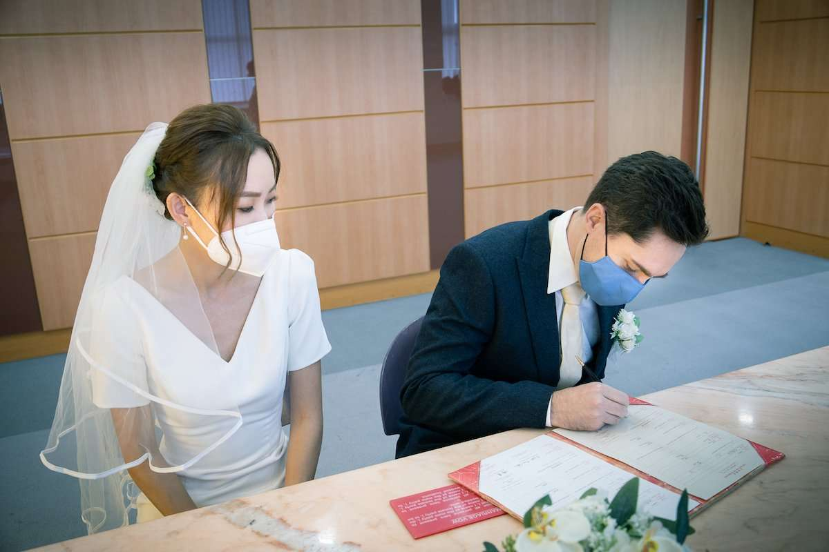Photograph of newlywed couple signing a registry, by AsiaPhoto photographer Lance Lee.