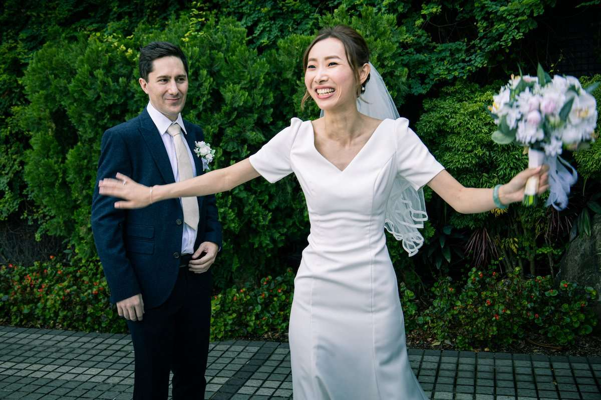 Photograph of newlywed couple, with bride preparing to toss a bouquet, by AsiaPhoto photographer Lance Lee.